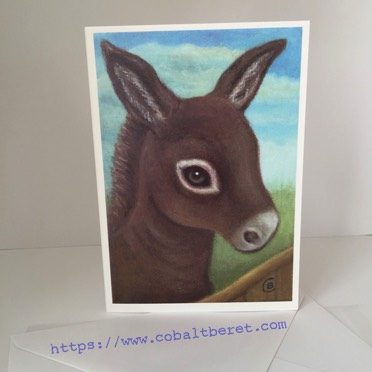 a greeting card of a little donkey looking over a fence